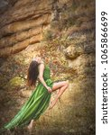 Small photo of sultry green-eyed flexible brunette in a long flying dress in the rocks
