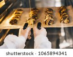 baker opens the oven with bread ... | Shutterstock . vector #1065894341