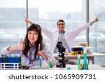 two chemists working in lab... | Shutterstock . vector #1065909731