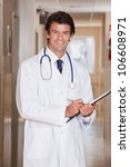 Male Doctor standing with folder at hospital. - stock photo