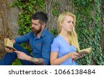 Small photo of Romantic vintage date concept. Couple in love sit back to back outdoor, nature background. Couple with busy faces reading poems. Romantic couple holds old book with poems about love.