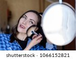 Small photo of Happy woman with cosmetic brush makeup round mirror is applied to the skin tone. makeup concept, real life