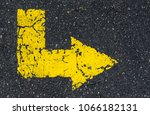 yellow arrow painted on tarmac | Shutterstock . vector #1066182131