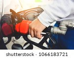 man holding red fuel nozzle and ... | Shutterstock . vector #1066183721