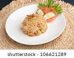 A Thai dish of fried rice with chicken presented on a round white plate. - stock photo