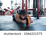 Small photo of Front look man using abdominal roller for working out abdominals