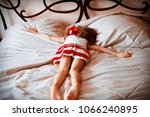 Small photo of little girl is lying on her parents bed along with her toy. divorce. girl is missing parents. unhappy family. abuse.