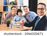 realtor in suit sitting at desk ... | Shutterstock . vector #1066320671