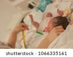 Small photo of just born baby is measured in hospital