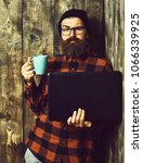 Small photo of Bearded man, long beard. Brutal caucasian serious unshaven hipster holding laptop with mag or cup in red black checkered shirt with hat and glasses on brown vintage wooden studio background