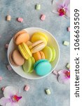 Small photo of Colorful cookies macarons on the plate and airy marshmallows. Light background