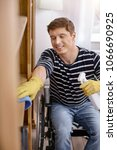 Small photo of Keep smiling. Happy male person keeping smile on face while cleaning room