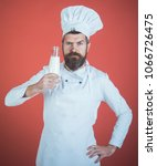 Small photo of Chef with confident face in white uniform presents milk. Best drink is milk. Man with beard and mustache holds bottle with milkshake or yogurt. Healthy food to your table. Nutritious lactose concept.
