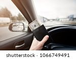 man with a purse and money in his hand behind the wheel of a car. drivers must pay for a toll on a toll highway - stock photo