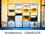 Old metal and glass warehouse door with sun reflections - stock photo