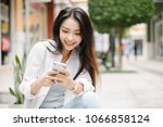 smiling woman using mobile...   Shutterstock . vector #1066858124