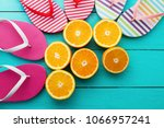 Summer fun time and flip flops. Slippers and orange fruit on blue wooden background. Mock up. Top view. Copy space