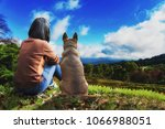 A Girl And Her Dog Sits On The...