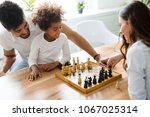 happy family playing chess... | Shutterstock . vector #1067025314