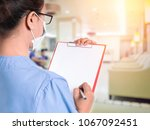 doctor filling out a medical... | Shutterstock . vector #1067092451