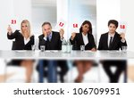 Group of panel judges holding bad score signs - stock photo