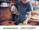 handsome barista preparing cup... | Shutterstock . vector #1067122007