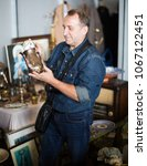 Small photo of Elderly man with camera consider things in flea market