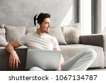 Small photo of Optimistic man 30s in basic clothing sitting on floor at home and looking aside with smile while using laptop and wireless headphones