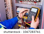 multimeter is in hands of... | Shutterstock . vector #1067283761