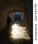 Small photo of A person is left in gloom as he passes through a passageway, which reflects with intensity the rays of the sun in the cobblestones of a street in a Portuguese city.