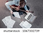 Small photo of Musical education. Top view of budding ambitious diligent man taking guitar while carrying note list and using laptop