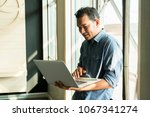 casual young man using laptop... | Shutterstock . vector #1067341274