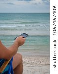 Small photo of young man sitting on lounge on the shore holds in hand mobile phone gadget resting sunbathing, looks at sea beach shore sand sky summer rest weekend