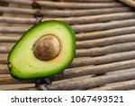 Small photo of cut green avocado with a ossicle on a woven wooden background