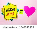 Small photo of Text sign showing Welcome 2018. Conceptual photo Celebration New Celebrate Future Wishes Gratifying Wish written on Yellow Sticky Note Paper on the plain background Pink Heart next to it.