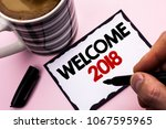 Small photo of Handwriting text writing Welcome 2018. Concept meaning Celebration New Celebrate Future Wishes Gratifying Wish written by Man on Sticky Note paper holding Marker plain background Coffee Cup