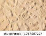 many footprints on sandy beach... | Shutterstock . vector #1067607227