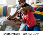 dad and son playing game at... | Shutterstock . vector #1067613644