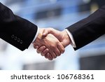 businessmen shaking hands on background of skyscrapers - stock photo