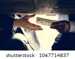 hands passing money under table ... | Shutterstock . vector #1067714837