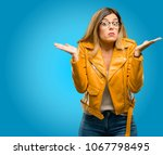 Small photo of Beautiful young woman doubt expression, confuse and wonder concept, uncertain future shrugging shoulders, blue background