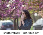 young pretty girl blowing nose... | Shutterstock . vector #1067835524
