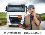 young truck driver with tablet | Shutterstock . vector #1067923574
