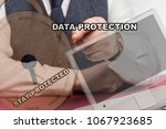 Small photo of Business man sitting behind desk pushing virtual screen with the words data protection and stay stay protected.