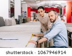 couple measuring mattress with... | Shutterstock . vector #1067946914