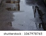 a puddle  with a cigarette bud... | Shutterstock . vector #1067978765