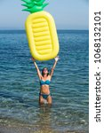 Small photo of Summer vacation concept. Woman catches above herself air mattress pineapple shaped, sea or ocean on background. Lady with air mattress stand in water, wearing stylish bikini and sunglasses.