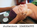 Small photo of The girl doing the facial massage . The cream on the face. Ayurvedic treatment. Spa treatments in Asia. Ayurveda salon