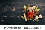 Small photo of Marinated cherry tomatoes in a jar. Stocks of food. Top view. On a wooden background. Copy space.