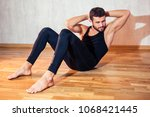 Small photo of A muscular man does exercises to strengthen the abdominal muscle